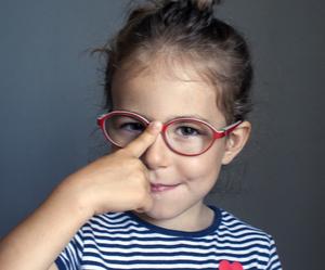 Une petite fille avec des lunettes qui souffre de strabisme